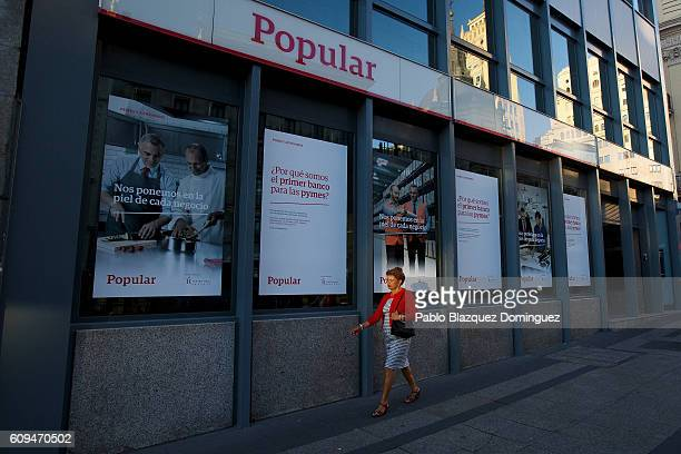 A woman walks past a Banco Popular branch on September 21 2016 in Madrid Spain Spain's Banco Popular plans to cut around 3000 jobs and close 300...