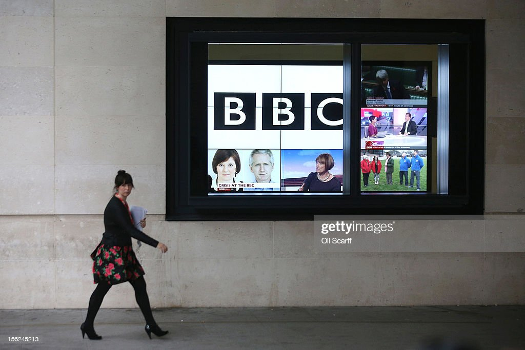 A woman walks past a bank of television screens displaying BBC channels in the BBC headquarters at New Broadcasting House on November 12, 2012 in London, England. Tim Davie has been appointed the acting Director General of the BBC following the resignation of George Entwistle after the broadcasting of an episode of the current affairs programme 'Newsnight' on child abuse allegations which contained errors.