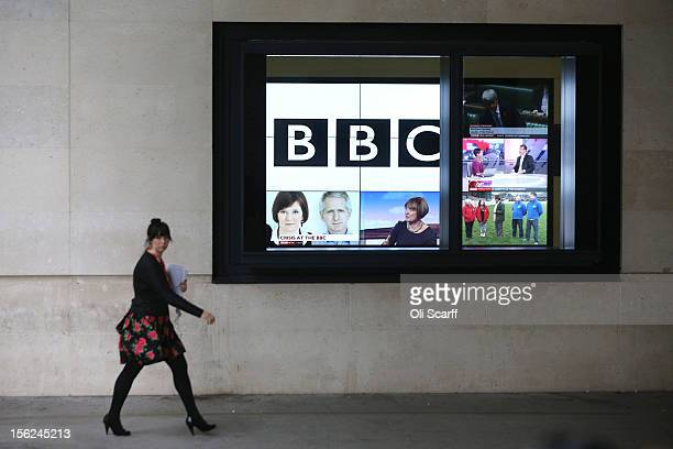 A woman walks past a bank of television screens displaying BBC channels in the BBC headquarters at New Broadcasting House on November 12 2012 in...