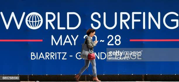 A woman walks past a banner announcing the 2017 ISA World Surfing Games on May 19 2027 in Biarritz southwestern France on the eve of the start of the...