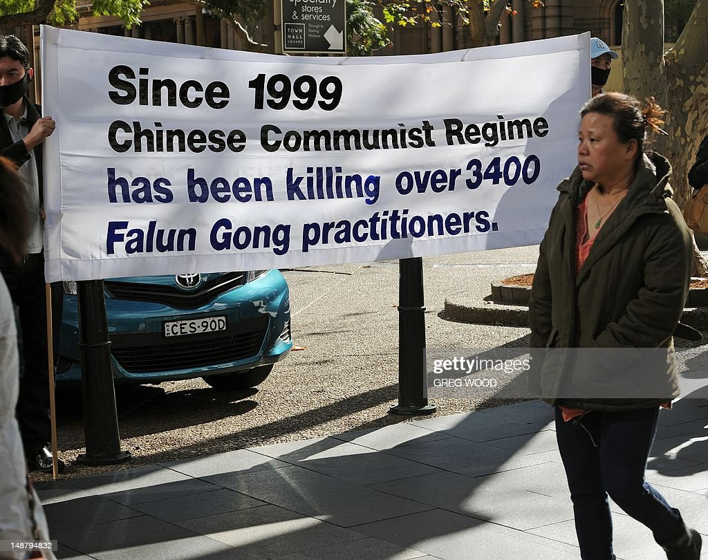 A woman walks past a banner as practitioners of spiritual movement Falungong gather at Sydney's Town Hall Square on July 20, 2012. The group intends to present an open letter to the Sydney office of Australian Prime Minister Julia Gillard urging her to denounce what they say is a 13-year-long persecution of the spiritual practice in China. Falungong -- a movement loosely based on Buddhist, Taoist and Confucian philosophies -- enjoyed growing popularity among the Chinese in the 1990s, but was banned by China in 1999 after thousands of practitioners silently converged in Beijing to air their grievances, showing their organizational might. AFP PHOTO / Greg WOOD