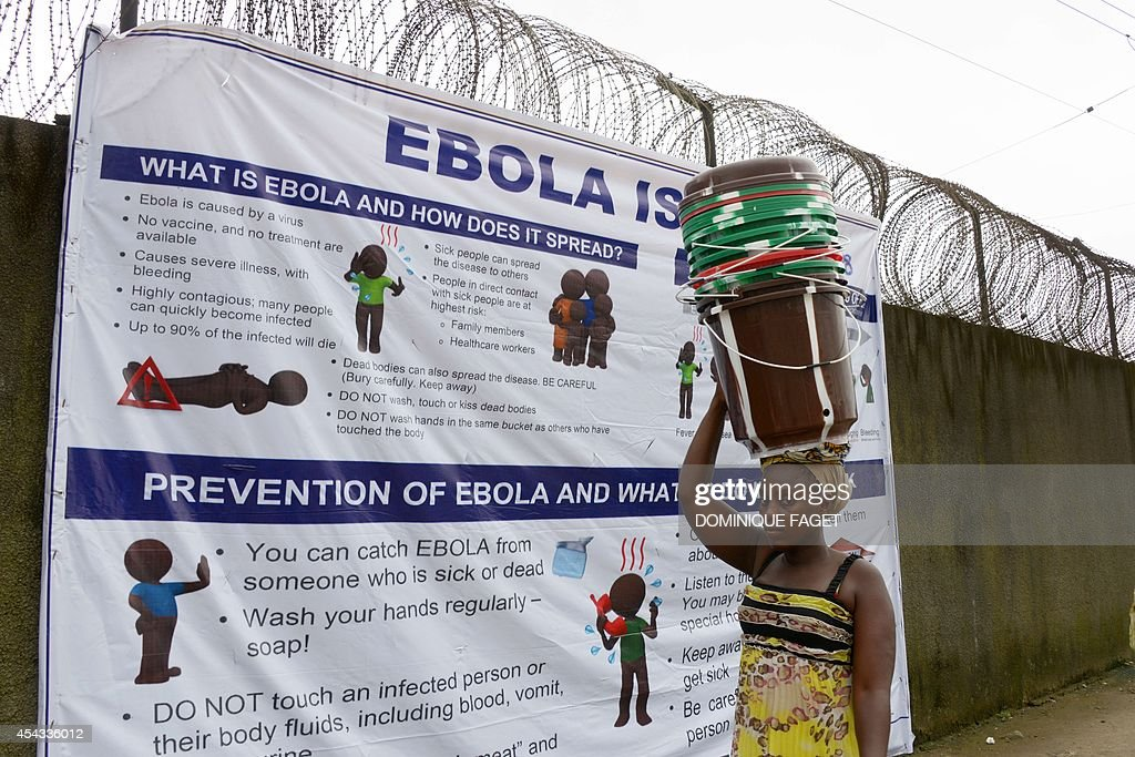 A woman walks past a banner informing about the Ebola virus near the entrance of the port of Monrovia on August 29, 2014. The World Health Organization said yesterday that the number of Ebola cases was increasing rapidly and could exceed 20,000 before the virus is brought under control, as the death toll topped 1,500.