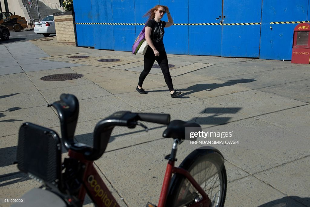 A woman walks past a bike share station and the Van Ness UDC metro during escalator repairs in the Metro transit system. / AFP / Brendan Smialowski