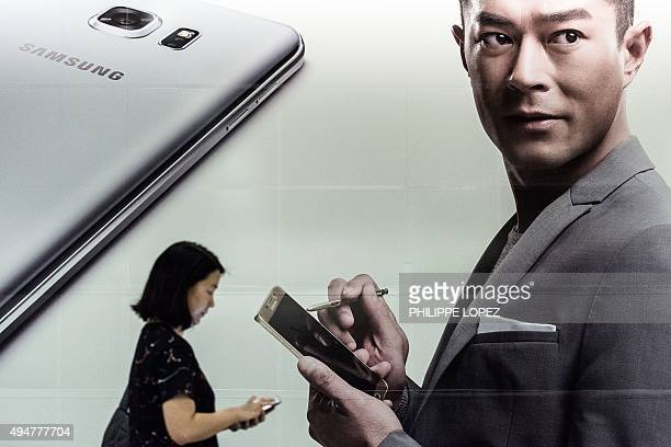 A woman walks past a billboard advertising for a Samsung mobile phone in Hong Kong on October 29 2015 South Korea's Samsung Electronics pulled out of...