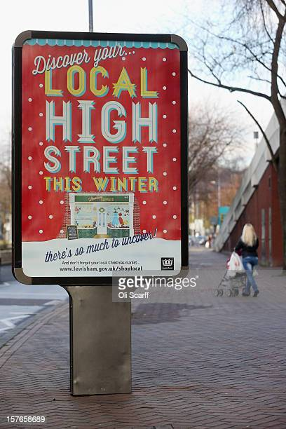 A woman walks past a billboard promoting Christmas shopping on local high streets on Lewisham high street on December 5 2012 in London England The...