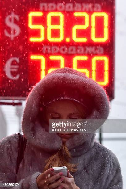 A woman walks past a board listing foreign currency rates against the Russian ruble outside an exchange office in central Moscow on December 12 2014...