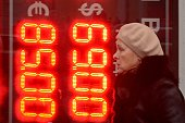 A woman walks past a board listing foreign currency rates against the Russian ruble outside an exchange office in central Moscow on December 16 2014...
