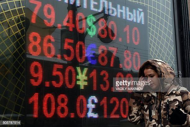 A woman walks past a board listing foreign currency rates against the Russian ruble in Moscow on January 20 2016 The ruble fell close to a historic...