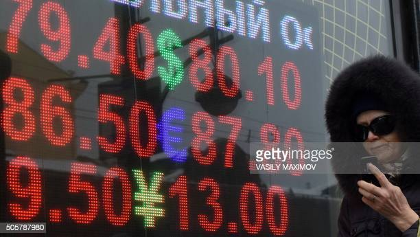 A woman walks past a board listing foreign currency rates against the Russian ruble in Moscow on January 20 2016 The ruble hit a historic low on...