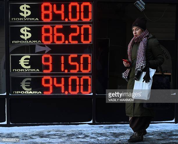 A woman walks past a board listing foreign currency rates against the Russian ruble in Moscow on January 21 2016 Russia's ruble today resumed its...
