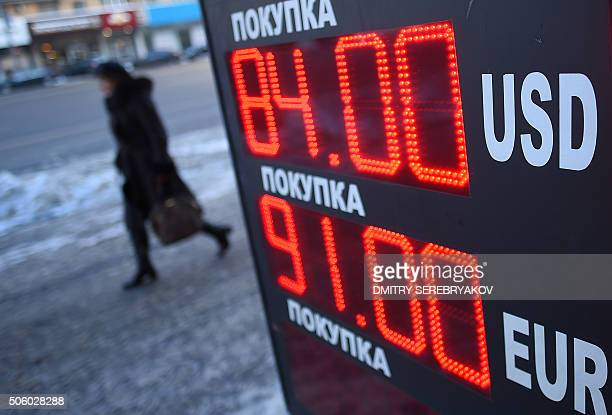 A woman walks past a board listing foreign currency rates against the Russian ruble in Moscow on January 21 2016 Russia's ruble resumed its slide to...