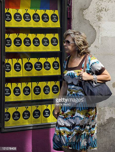 A woman walks past a bookshop window displaying Christopher Hitchens's book 'God is not great' in Madrid on August 17 on the eve of Pope Benedict...