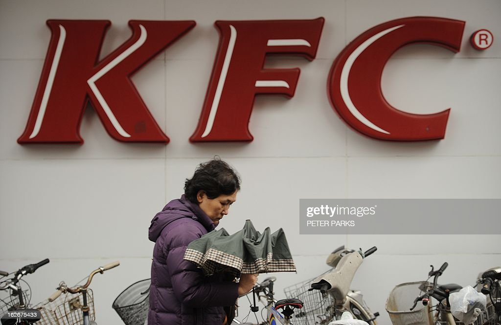A woman walks past a branch of a KFC restaurant in Shanghai on February 26, 2013. The fast food giant has cut more than 1,000 farms from its supplier network in China to ensure food safety after a scandal over tainted chicken hurt sales in the key market last year. AFP PHOTO/Peter PARKS