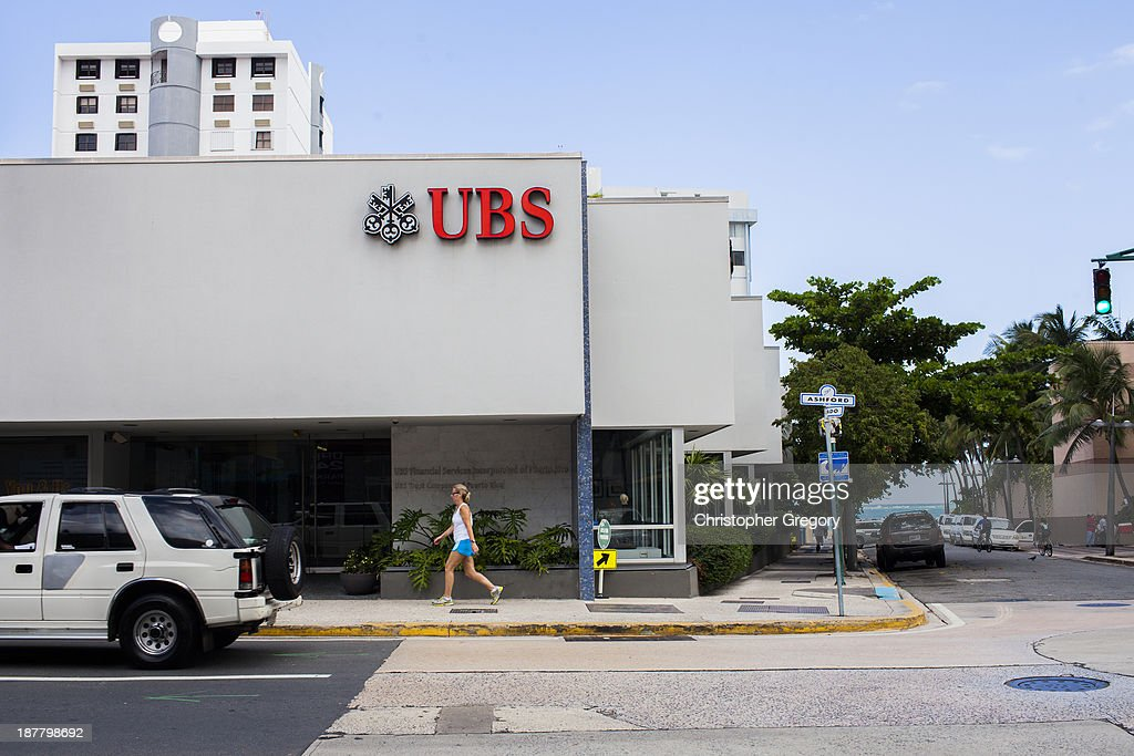 A woman walks past a branch of Swiss bank UBS, which manages close to half of Puerto Rico's wealth, on November 12, 2013 in the Condado neighborhood of San Juan, Puerto Rico. The island territory of the United States, Puerto Rico, is on the brink of a debt crisis as lending has skyrocketed in the last decade as the government has been issuing municipal bonds. Market analysts have rated those bonds as junk and suspect it's 70 billion dollar debt might be unserviceable in the near future. With no industry other than tourism and the recent collapse of the real estate market, the way out is unclear.