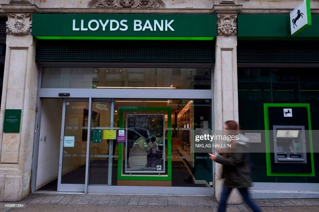 A woman walks past a branch of the British bank Lloyds in London on October 22 2015 Britain's Competition and Markets Authority released its...