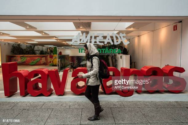 A woman walks past a Brazilian Havaianas flipflops store in Sao Paulo Brazil on July 18 2017 The Havaianas ambassadors of Brazil in the world were...