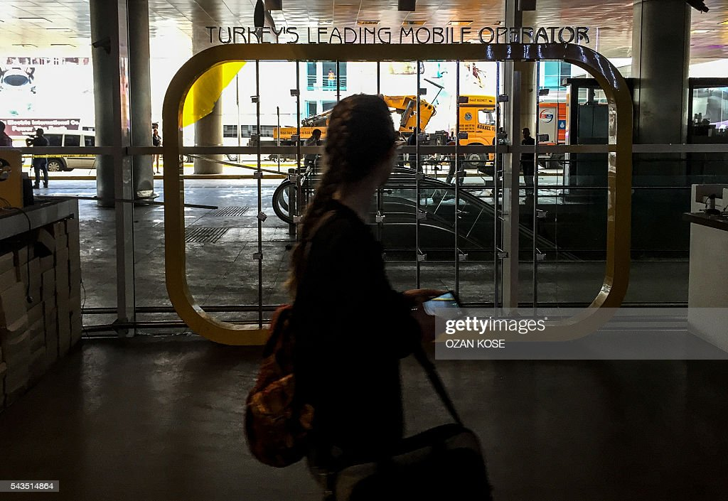 A woman walks past a broken window at the explosions and attacks site outside Ataturk airport's international arrivals terminal on June 29, 2016, a day after a suicide bombing and gun attack targeted Istanbul's airport, killing at least 36 people. A triple suicide bombing and gun attack that occurred on June 28, 2016 at Istanbul's Ataturk airport has killed at least 36 people, including foreigners, with Turkey's prime minister saying early signs pointed to an assault by the Islamic State group. / AFP / OZAN