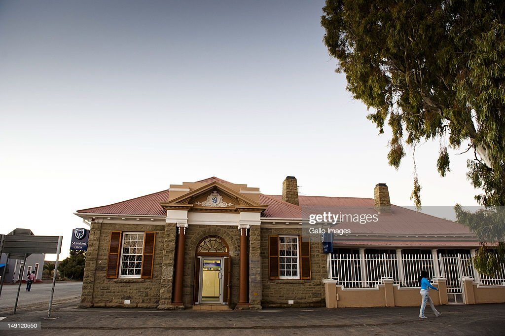A woman walks past a building in Carnarvon on July 20, 2012 in the Northern Cape, South Africa. The town, which has a population of 6000, is the home of the KAT-7 telescope and will host the Square Kilometre Array radio telescope. Due to these developments the town's economy is growing.