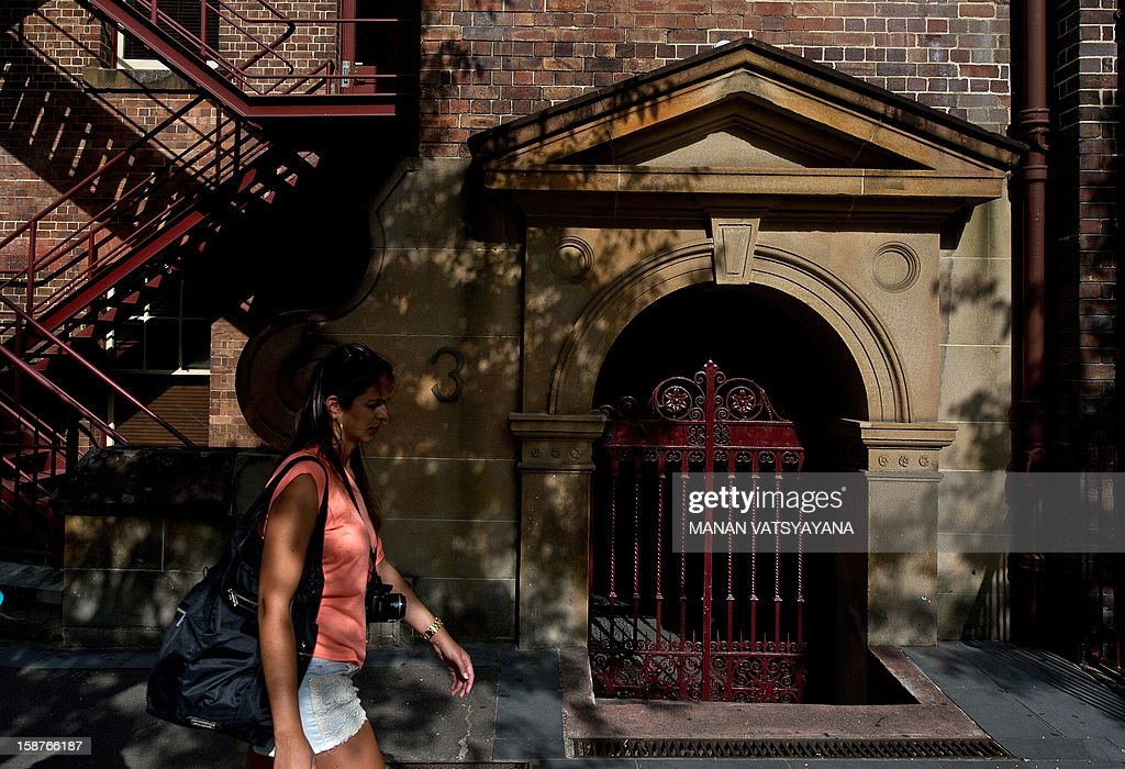 A woman walks past a building in the historic rocks area of Sydney on December 28, 2012. International visitors to Australia are expected to increase from over 5.9 million in 2010/11 to nearly 8.2 million in 2020/21, an average annual growth rate of 3 percent as reported from Tourism Research Australia (TRA).