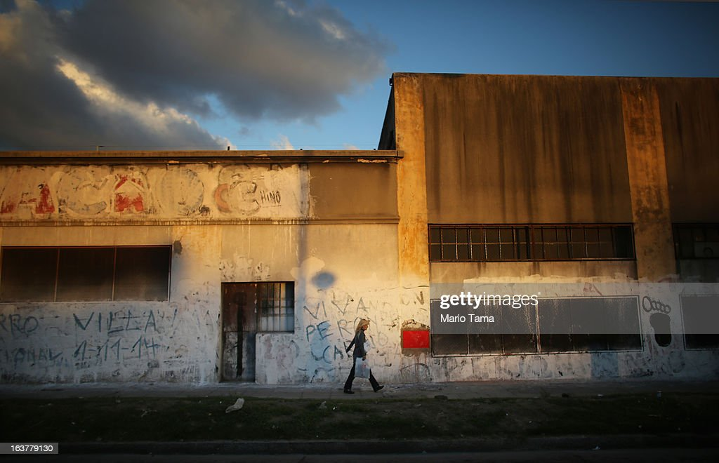 A woman walks past a building marked with graffitti in the Bajo Flores neighborhood, where archbishop Jorge Mario Bergoglio, now Pope Francis, used to perform charity work, two days after Francis was elected at the Vatican on March 15, 2013 in Buenos Aires, Argentina. Francis was the archbishop of Buenos Aires, and is the first pope to hail from South America. Some locals are now affectionately calling Francis, known for his charity work in the slums, the 'slum pope.'