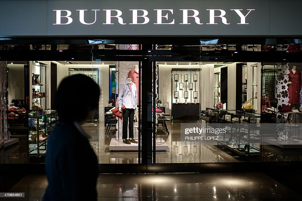 A woman walks past a Burberry store in Hong Kong on February 21, 2014. A brazen shoplifter has helped himself to an alligator-leather coat worth nearly HKD1 million (USD130,000) from a flagship Burberry store in one of Hong Kong's busiest shopping districts, police said on February 21. AFP PHOTO / Philippe Lopez