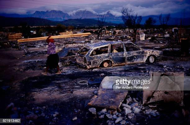 A woman walks past a burned out car and shacks in a poor township in Strand Cape Town South Africa A fire burned down about 300 shacks a day earlier...