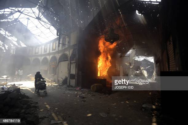 A woman walks past a burning shop in the Maskuf market in the Old City of Homs some 162 kilometres north of the capital Damascus on May 12 2014...