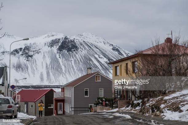 A woman walks past a cafe and houses in the town of Borgarnes at the foot of mountains on March 27 2017 at Borgarnes Iceland Iceland's economy has...