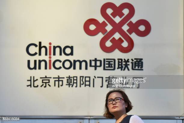 A woman walks past a China Unicom sign in Beijing on August 17 2017 A plan under which big Chinese companies led by Tencent and Alibaba would invest...