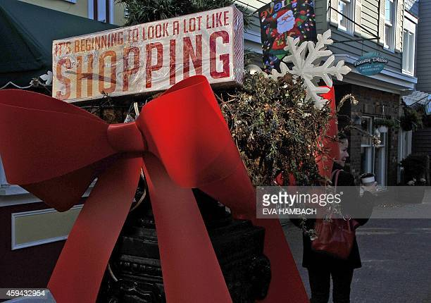 A woman walks past a Christmas bow in a shopping mall in Rehoboth Beach Delaware November 22 2014 Christmas decorations are already being displayed...