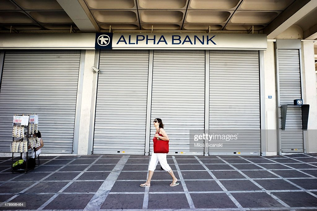 A woman walks past a closed bank on June 29 2015 in Athens Greece Greece closed its banks and imposed capital controls on Sunday to check the growing...