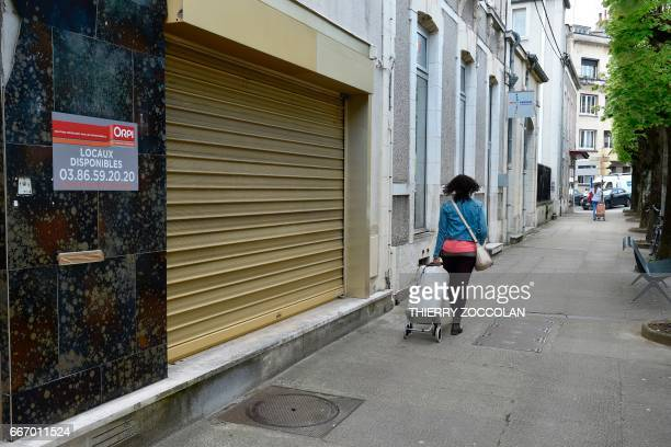 A woman walks past a closed business in Nevers central France on April 4 2017 The population of the picturesque town on the Loire river has fallen by...