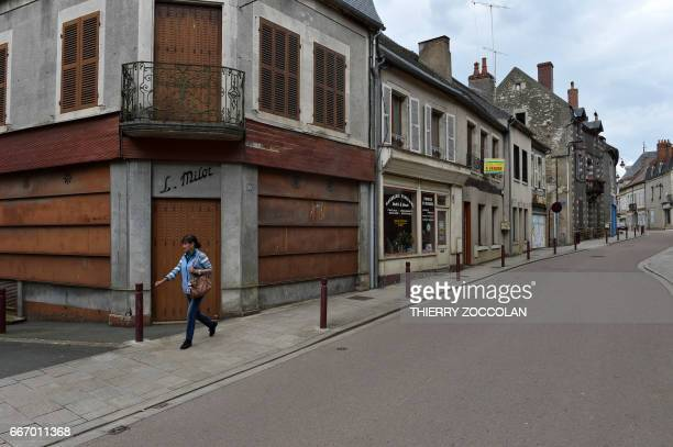 A woman walks past a closed business in Varzy central France on April 4 2017 With its deserted streets 'For Sale' signs and weeds pushing through the...