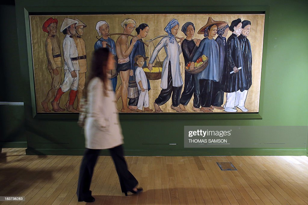 A woman walks past a colonial painting displayed at the exhibition 'Indochine, des territoires et des hommes 1856-1956' (Indochina, of territories and men) at the Army Museum (Musee de l'armee) on October 9, 2013, at the Hotel National des Invalides in Paris. The exhibiton runs from October 16 to January 26, 2014.