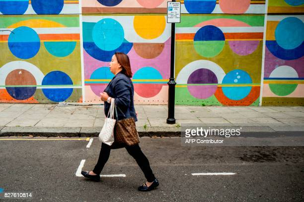 A woman walks past a colourful wall near the Portobello Road Market in the Notting Hill district of west London on August 8 2017 Last week The Bank...