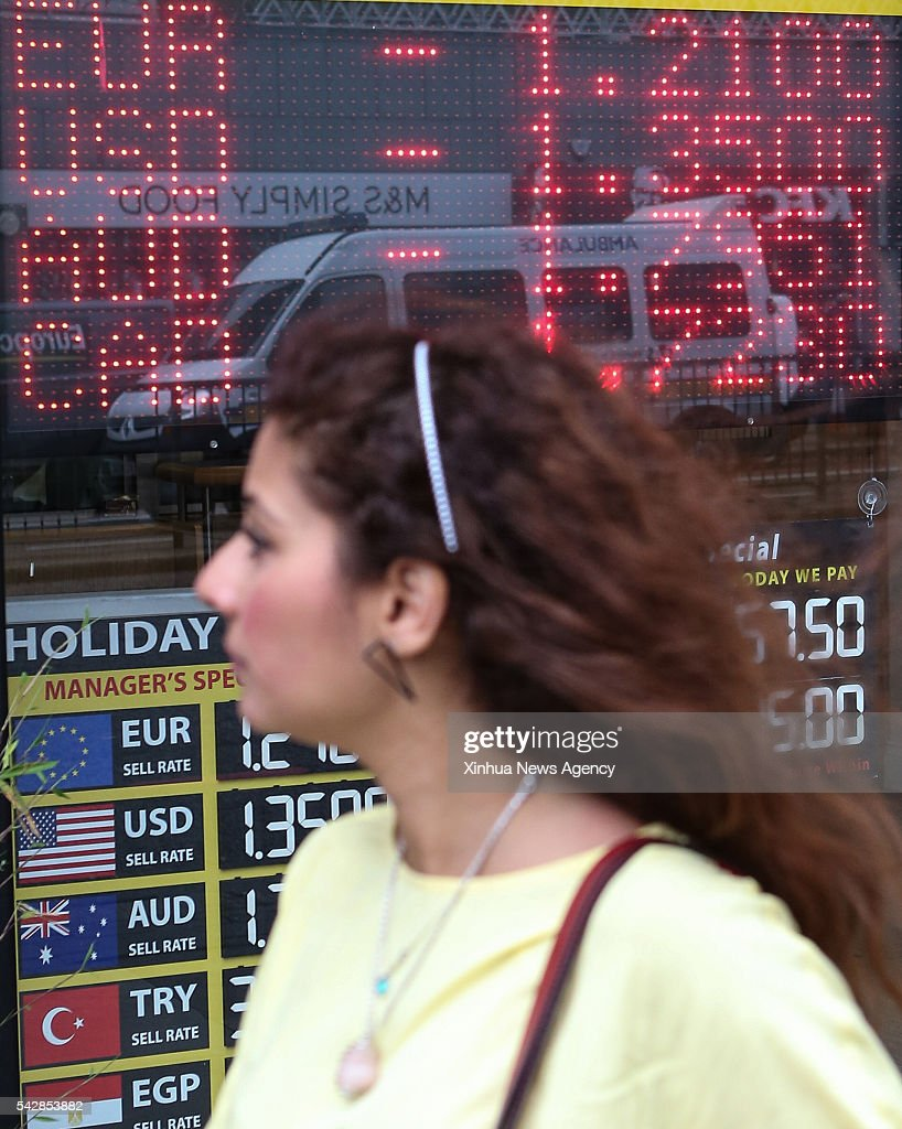 A woman walks past a currency exchange shop in London, Britain, on June 24, 2016.