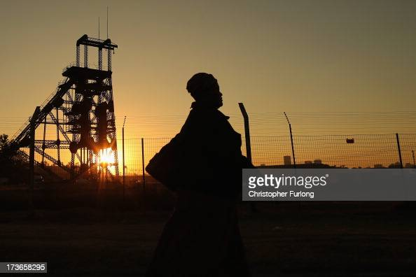 A woman walks past a derelict gold mine shaft's winding gear in front of the setting sun on July 15 2013 in Johannesburg South Africa Johannesburg...