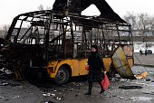 A woman walks past a destroyed bus in Donetsk on February 11 2015 Shelling hit a central bus station in Donetsk on February 11 2015 and killed at...