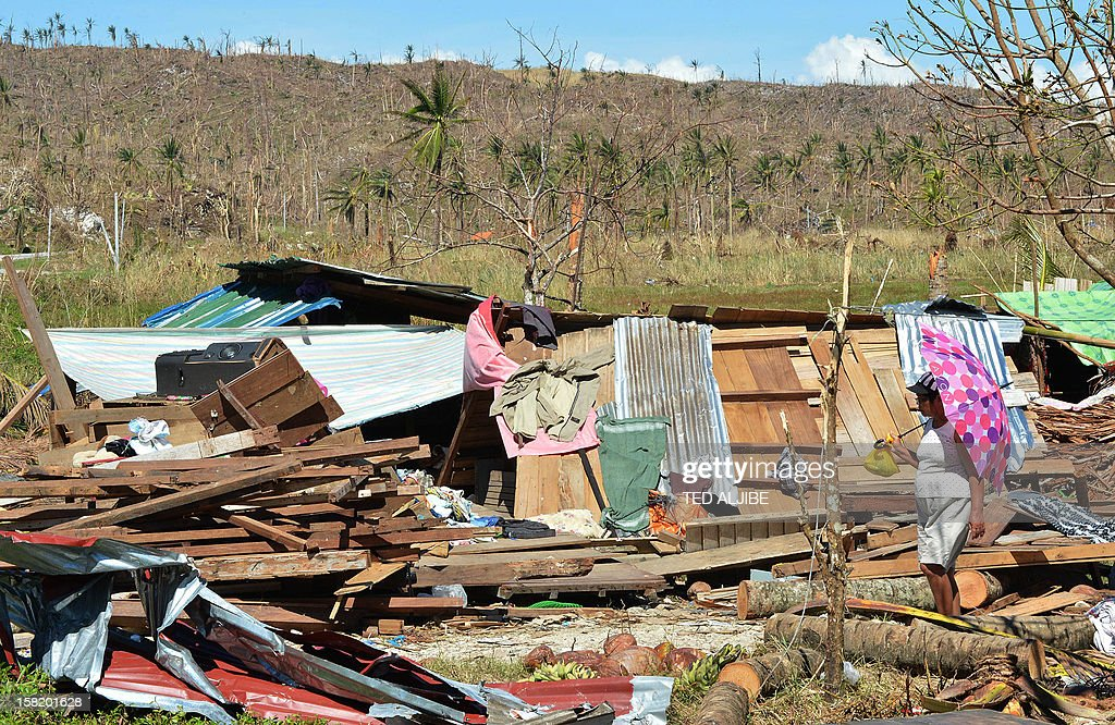A woman walks past a destroyed house in a village of Cateel town, Davao Oriental province on December 11, 2012. The United Nations launched a 65 million USD global appeal on December 10 to help desperate survivors of a typhoon that killed more than 600 people and affected millions in the southern Philippines. AFP PHOTO/TED ALJIBE