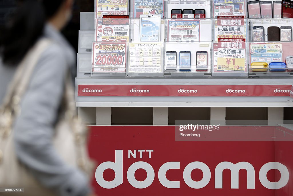 A woman walks past a display of mock-up mobile devices at a counter for NTT Docomo Inc. outside an electronics store in Tokyo, Japan, on Wednesday, Oct. 23, 2013. DoCoMo, Japan's largest mobile phone carrier, is scheduled to release earnings results on Oct. 25. Photographer: Kiyoshi Ota/Bloomberg via Getty Images