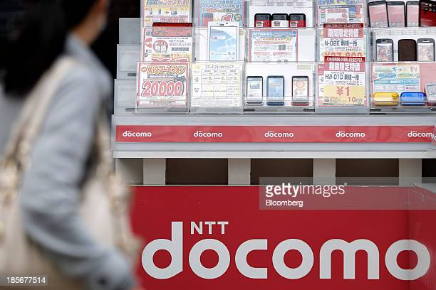 A woman walks past a display of mockup mobile devices at a counter for NTT Docomo Inc outside an electronics store in Tokyo Japan on Wednesday Oct 23...
