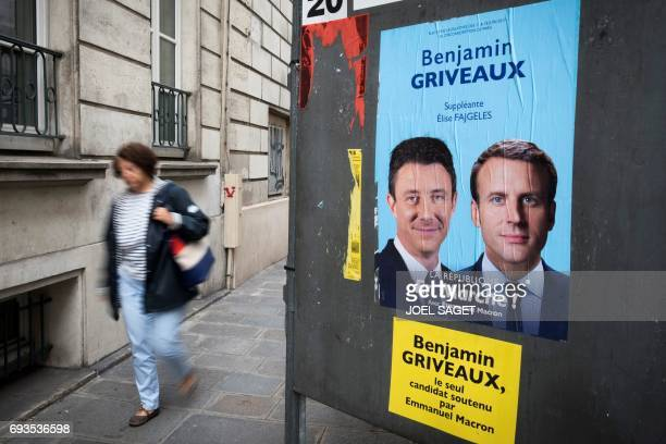 A woman walks past a electoral campaign poster for French President Emmanuel Macron and Benjamin Griveaux La Republique En Marche's spokesperson and...