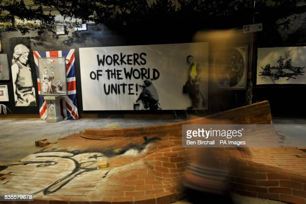 A woman walks past a fallen and warped brick wall with more works of art in the background at Bristol Museum where artist Banksy is exhibiting his...