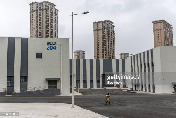 A woman walks past a film studio building as residential buildings stand in the background inside the Dalian Wanda Group Co Oriental Movie Metropolis...