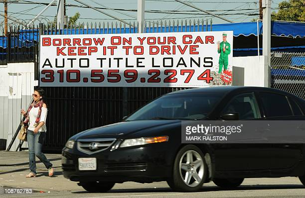 A woman walks past a firm offering cash loans which use your car as collateral in Los Angeles on February 02 2011 The United States is poised to hit...
