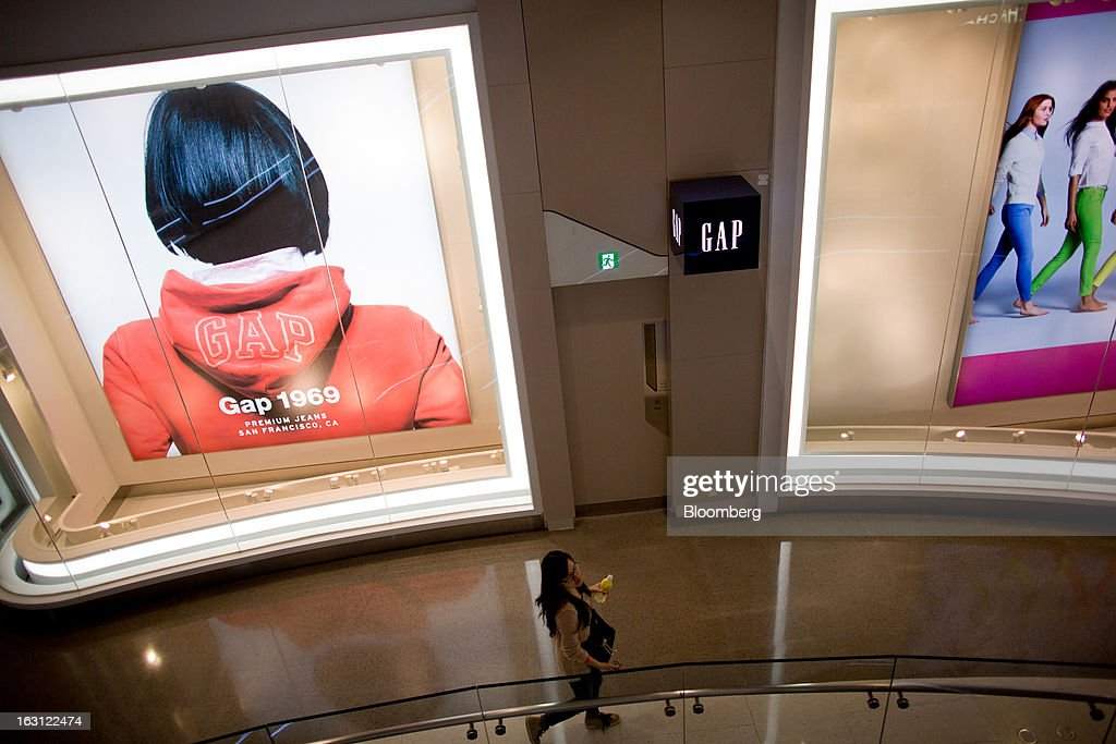A woman walks past a Gap Inc. store at Hysan Development Co.'s Hysan Place mall in the Causeway Bay district of Hong Kong, China, on Monday, March 4, 2013. Hysan is scheduled to release earnings on March 6. Photographer: Lam Yik Fei/Bloomberg via Getty Images
