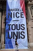 A woman walks past a giant poster which translates as 'ALL UNITED' and diplayed in tribute to the victims of the deadly Nice attack on Bastille day...