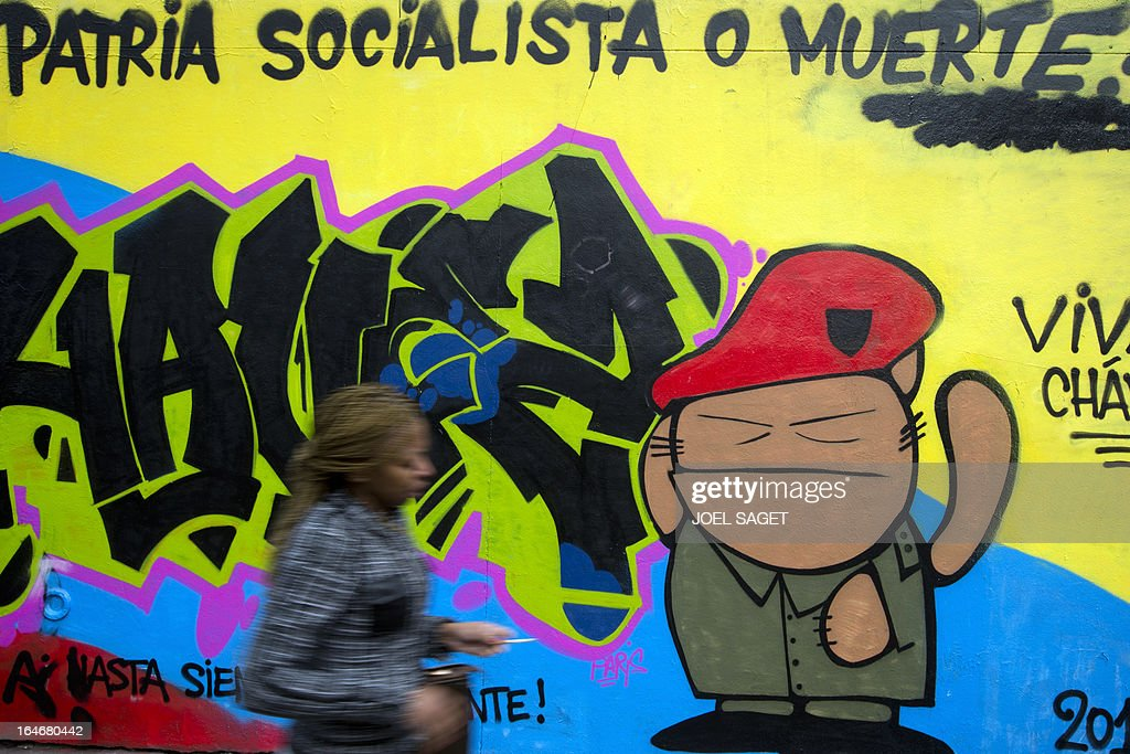 A woman walks past a graffiti mocking Venezuela's late president Hugo Chavez on March 26, 2013 in Paris. AFP PHOTO/ JOEL SAGET