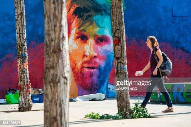 A woman walks past a graffiti portraying Barcelona's Argentinian forward Lionel Messi in Barcelona on June 17 2017 / AFP PHOTO / Josep LAGO
