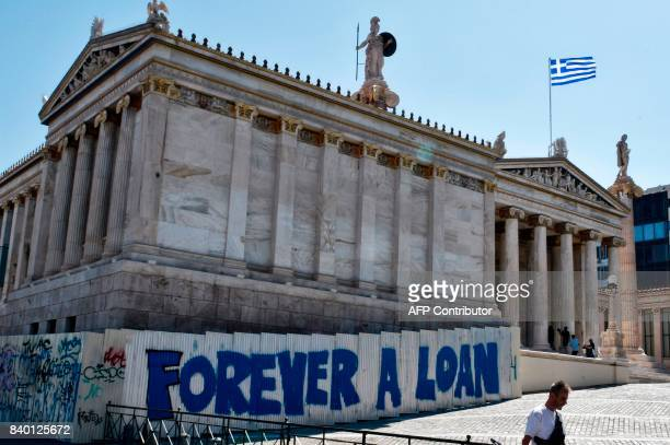 A woman walks past a graffiti refering to the Greek debt and reading 'Forever a loan' outside the Academy of Athens building on August 28 2017 / AFP...